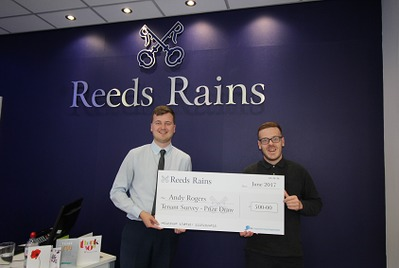 Winner of prize draw in front of Reeds Rains branch