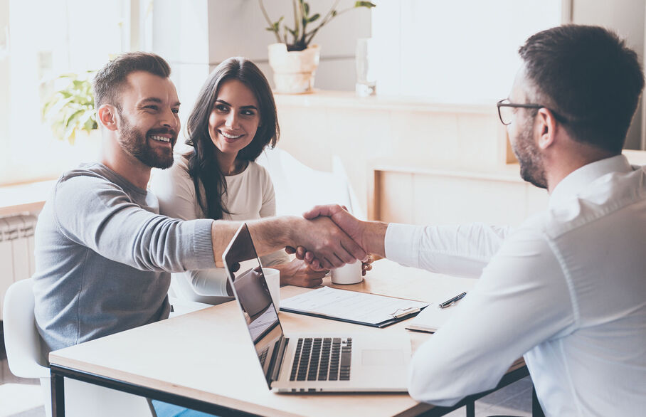 Couple shaking hands with an adviser