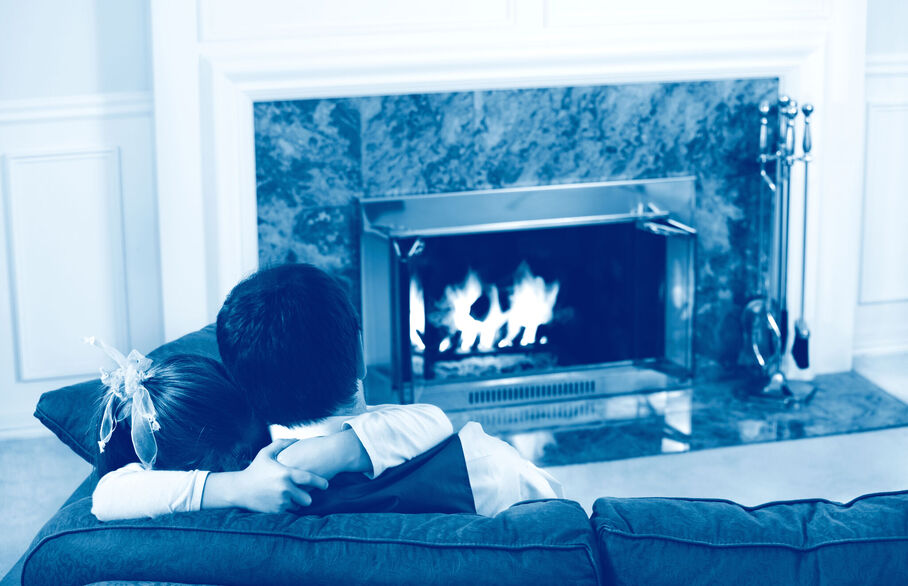 Couple on the sofa in front of a fireplace