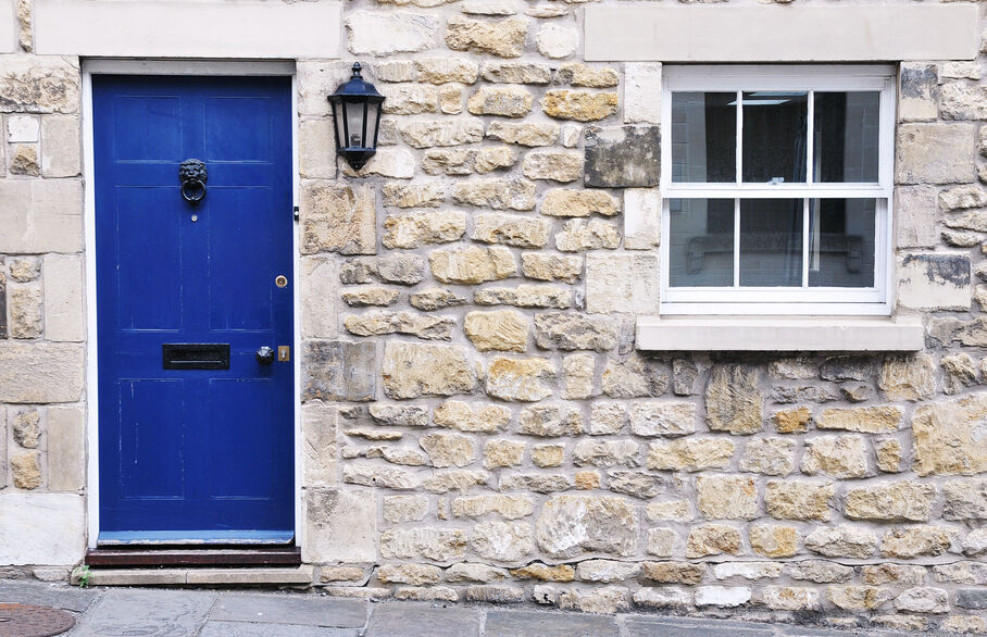 Front of a stone built house with closed blue door