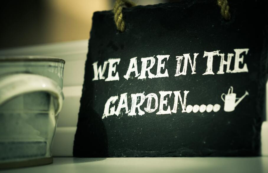 Chalkboard style sign showing 'We are in the garden'.