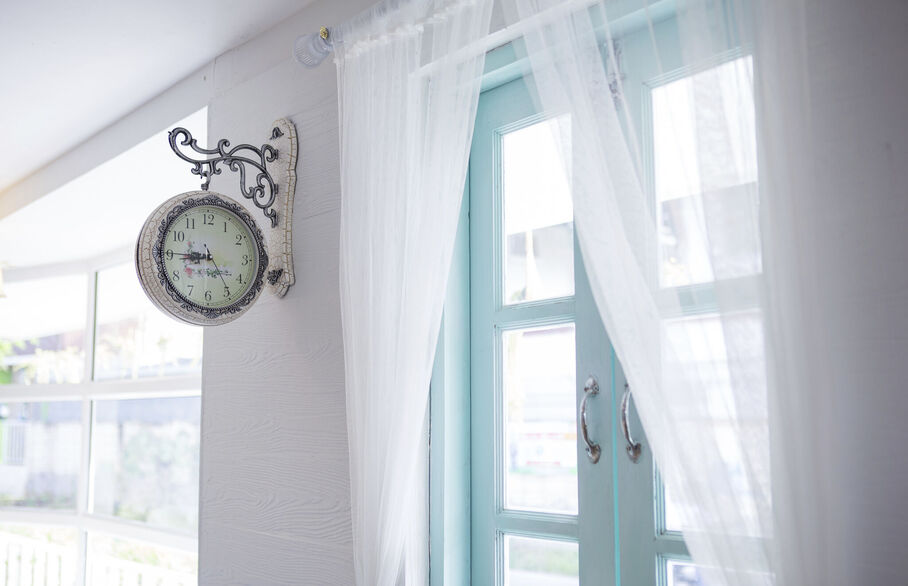 Clock on the wall in front of windows