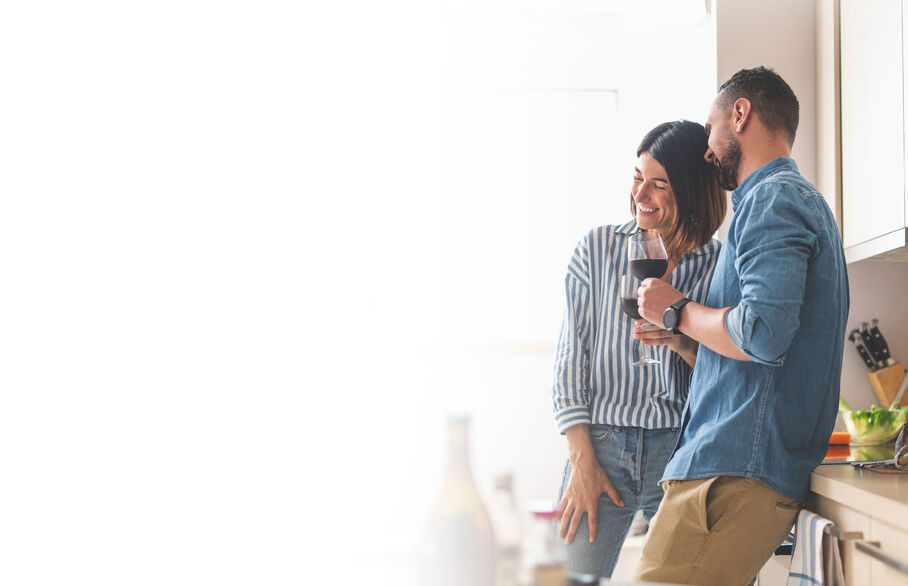 Couple leaning against kitchen tops with glasses of red wine