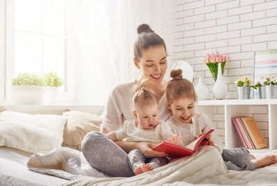 Family sat on the bed reading a book