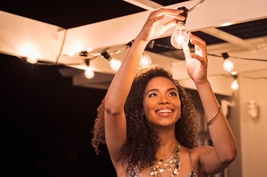 Lady plugging in a bulb to outside lights