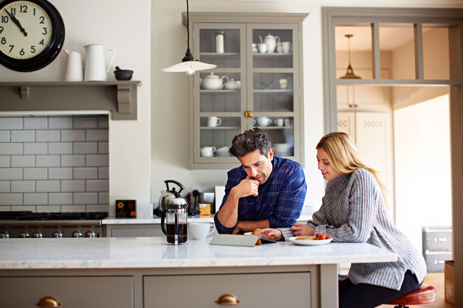 Couple in a kitchen looking at a laptop