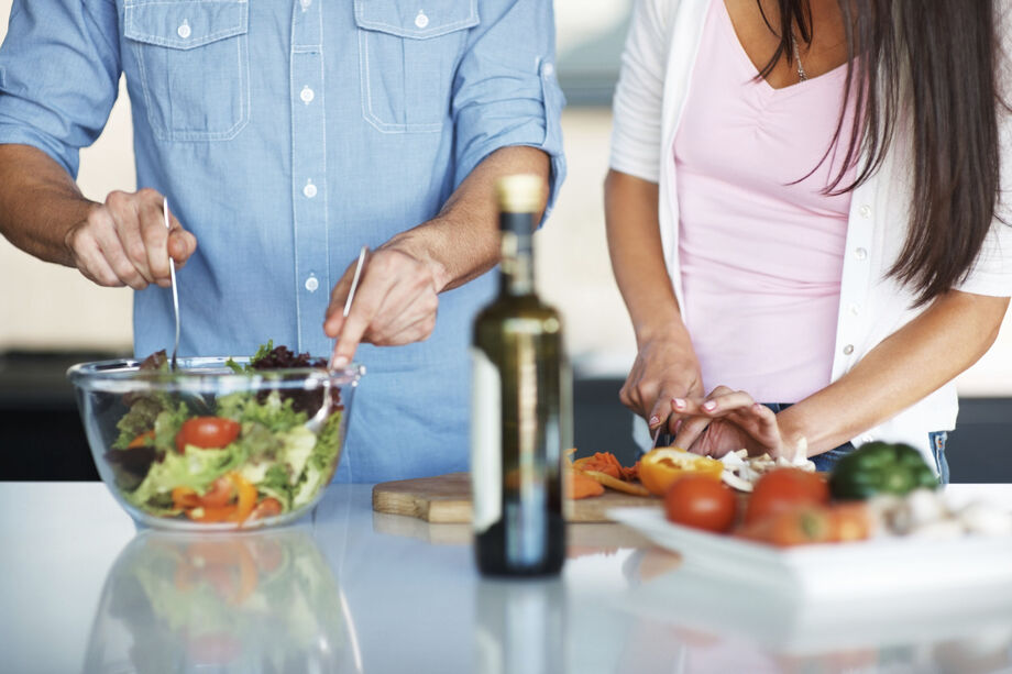 Couple in the kitchen making salad