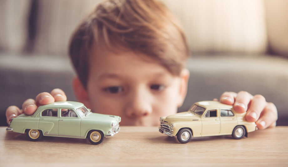 Little boy playing with two vintage cars